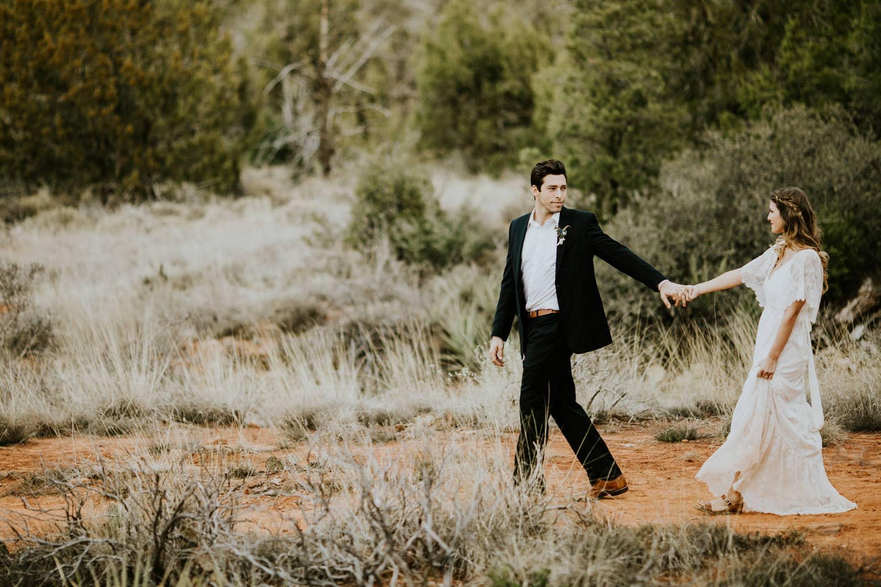 groom leading bride in sedona desert