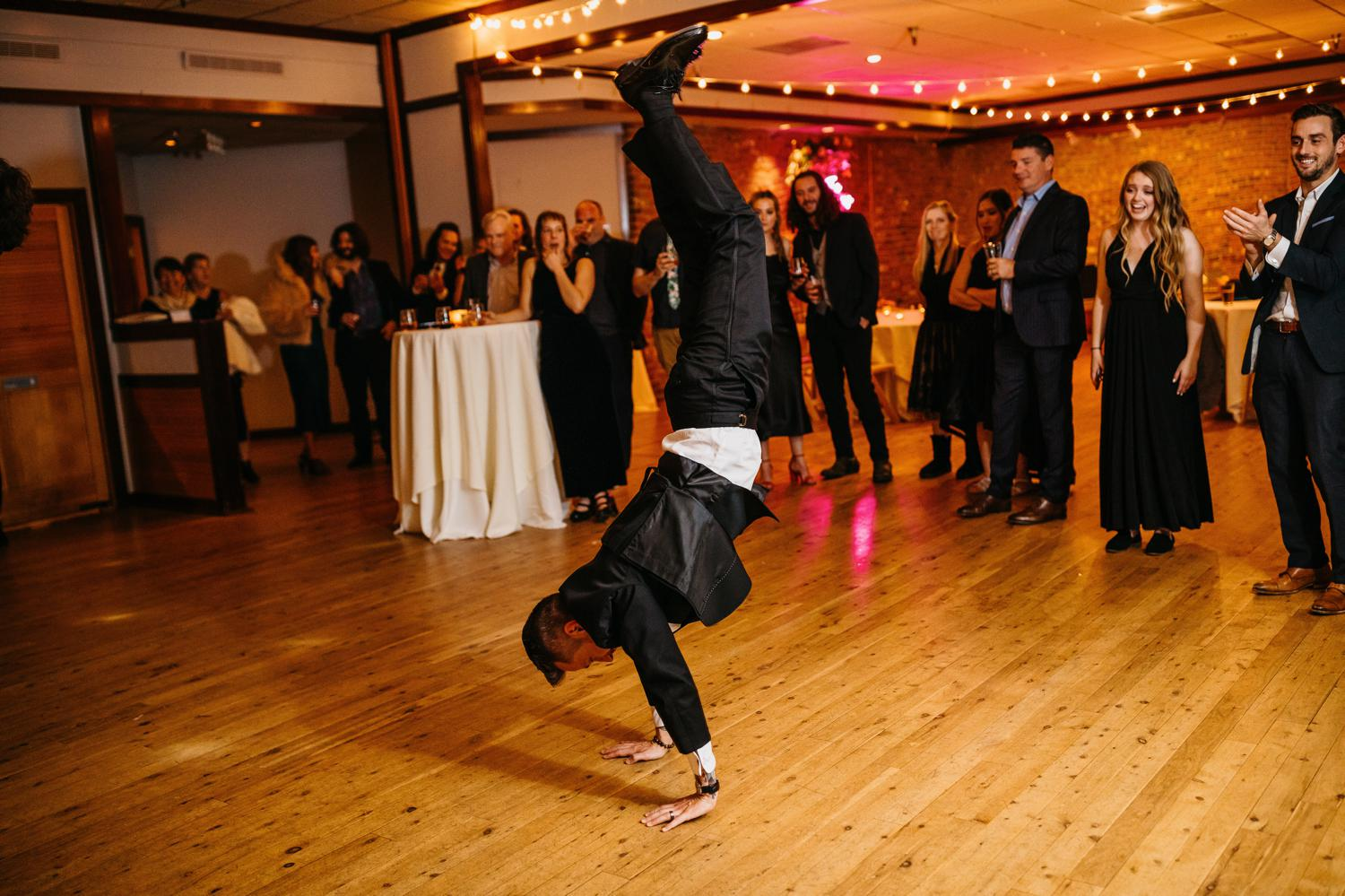 groom doing handstand at wedding reception